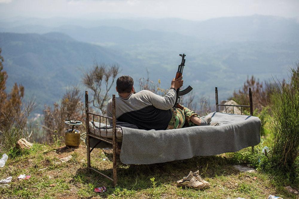 Soldado sírio deitado na cama no morro perto da cidade de Kesab