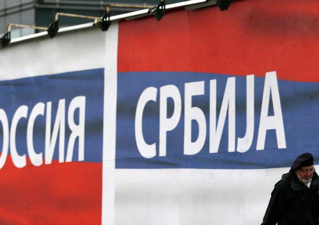 Um homem passa perto da cartaz com inscrições Rússia e Sérvia, 17 de outubro de 2014