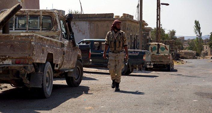 Combatente do exército sírio livre anda perto de veículos militares, Síria, 30 de setembro de 2015
