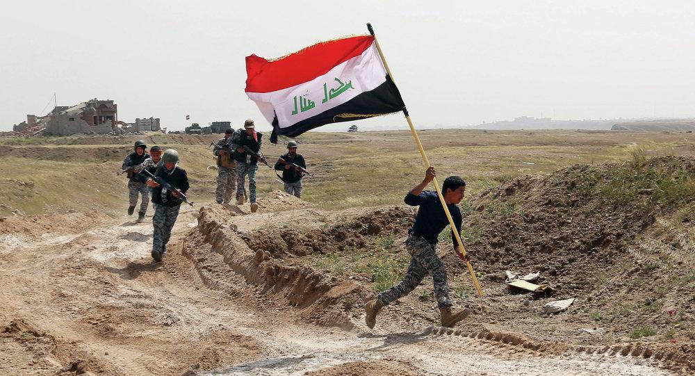 Integrante das forças de segurança do Iraque corre com a bandeira do país após país cercar Tikrit, tomada pelo Estado Islâmico