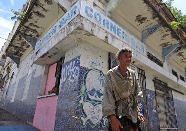 Homem sem casa porto-riquenho perto duma empresa fechada nos arerdores de São João, Porto Rico, 2 de agosto de 2015