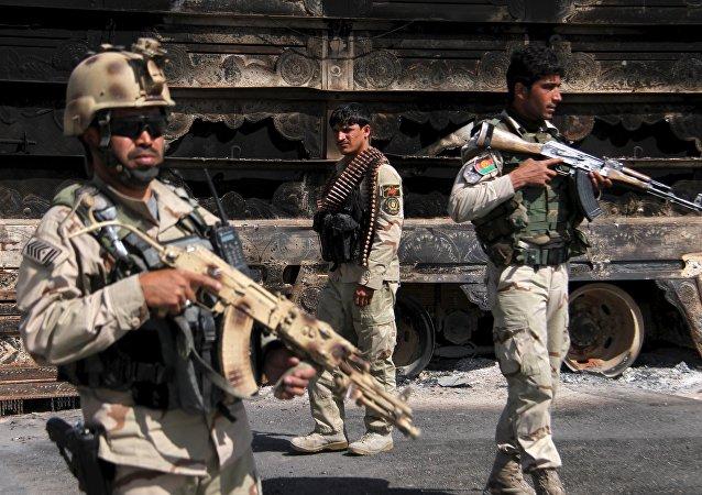 Forças de segurança afegãs mantêm vigilância enquanto veículo pega fogo na rodovia Kabul-Kandahar após embate entre as forças do governo e militantes do Talibã em  14 de outubro de 2015.