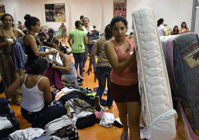 Pessoas trazem suprimentos para o ginásio Arena Mariana, onde ficarão abrigadas as vítimas da inundação, provocada pelo rompimento da barragem