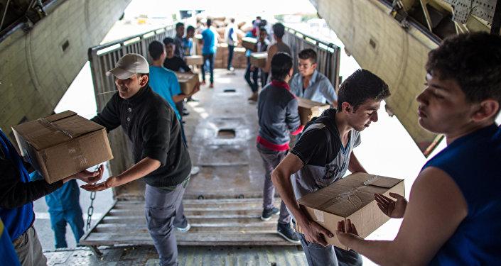 Pessoas descarregando avião russo EMERCOM com ajuda humanitária que chegou ao aeroporto de Latakia na Síria