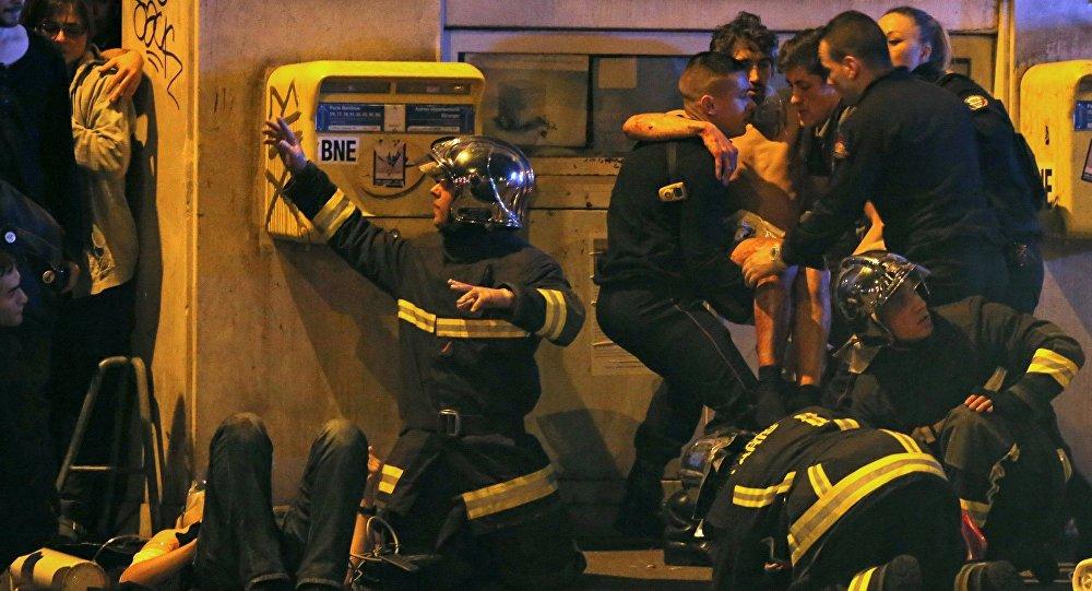 Bombeiros ajudam uma pessoa ferida perto do teatro Bataclan