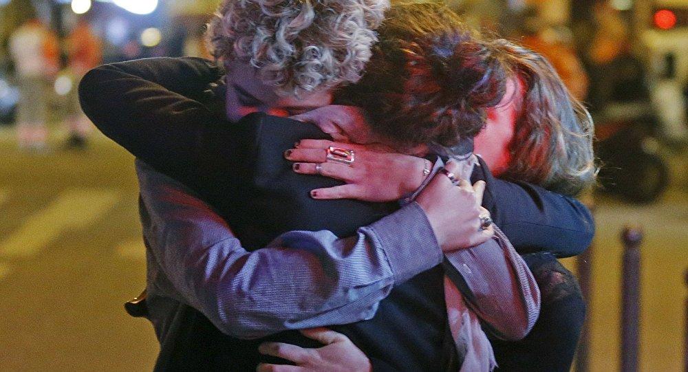 Três sobreviventes se dão um abraço fora da sala de concertos Bataclan, onde tinha acontecido um ataque com fuzil automático
