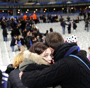 Um casal se abraça no estádio Stade de France, depois do amistoso França-Alemanha.