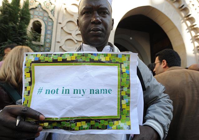 Foto de arquivo de um homem com o cartaz Não em meu nome, durante uma manifestação convocada por grupos muçulmanos a denunciar a barbárie dos militantes do Estado Islâmico, em 26 de setembro de 2014 fora a principal mesquita de Paris