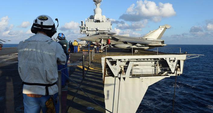 Técnicos franceses perto do caça Rafale no convés do porta-aviões Charles de Gaulle no Mediterrâneo