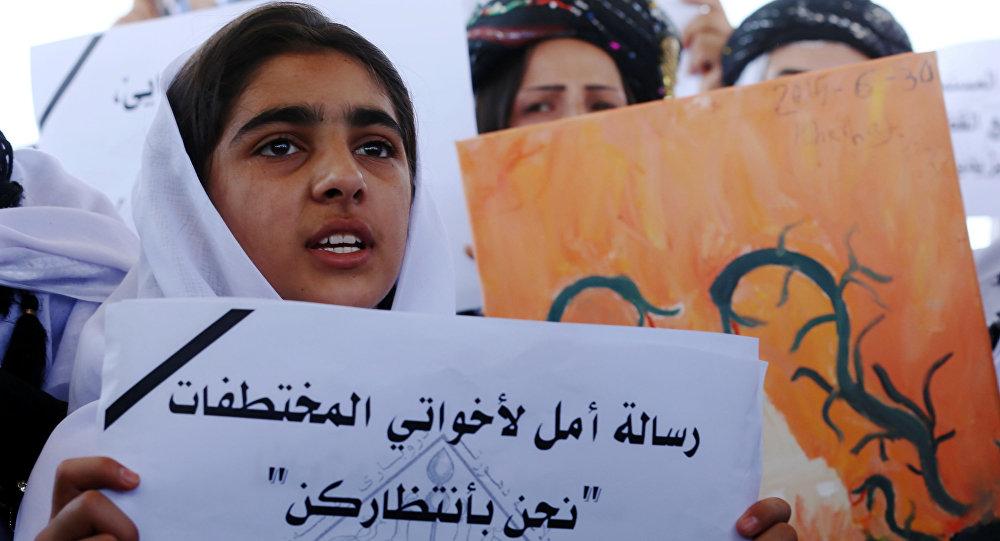 Menina yazidi empunha um cartaz que diz Mensagem de esperança para a minha irmã: estamos à tua espera durante o protesto perto do escritório da ONU em Arbil, capital da região autónoma de Curdistão, Iraque, 2 de agosto de 2015
