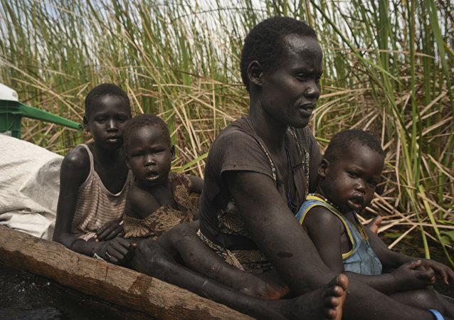 Uma mulher usa uma canoa para fugir com seus filhos de uma região pantanosa no Sudão do Sul.