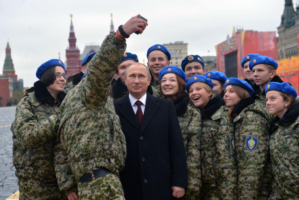 Presidente da Rússia Vladimir Putin é fotografado com os membros do centro militar-patriótico Vympel durante a cerimônia de colocar flores para o monumento a Kuzma Minin e Dmitry Pozharsky na Praça Vermelha.
