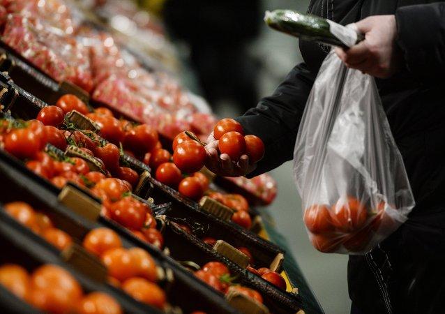 Comprador no supermercado russo escolha tomates