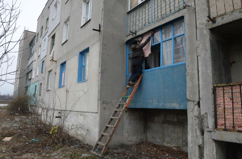 Homem tenta reparar janelas quebradas em Debaltsevo
