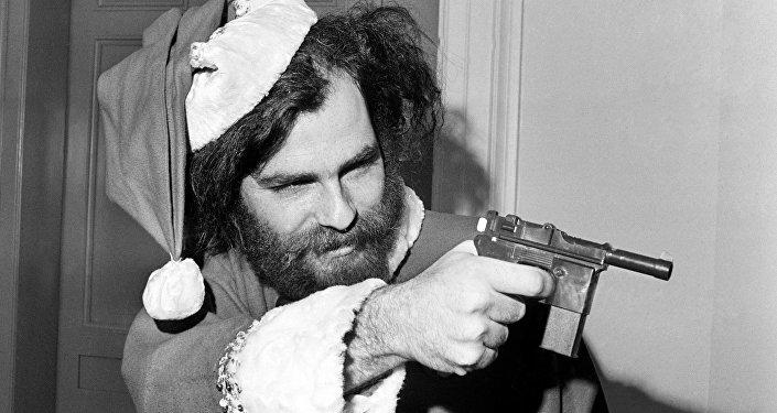 """O líder do Partido Internacional da Juventude, Jerry Rubin, aponta uma arma de brinquedo em sinal de """"defesa legítima"""" em 4 de dezembro de 1969, ao ser proibido de participar da sessão do subcomitê de Atividades Antiamericanas. Rubin chegou à sessão vestido de Santa para demostrar que o subcomitê era """"um circo total""""."""