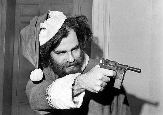 """O líder do Partido Internacional da Juventude, Jerry Rubin, aponta uma arma de brinquedo em sinal de """"defesa legítima"""" em 4 de dezembro, ao ser proibido de participar da sessão do subcomitê de Atividades Antiamericanas. Rubin chegou à sessão vestido de Santa para demostrar que o subcomitê era """"um circo total"""""""