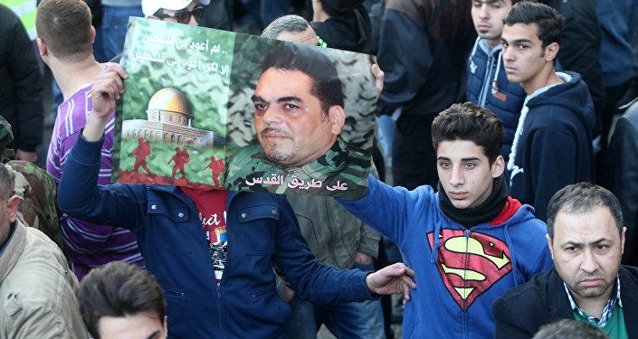 Cidadãos libaneses empunham um cartaz com o retrato de Samir Kuntar durante a cerimónia de funerais do membro do Hezbollah, Beirute, Líbano, 21 de dezembro de 2015