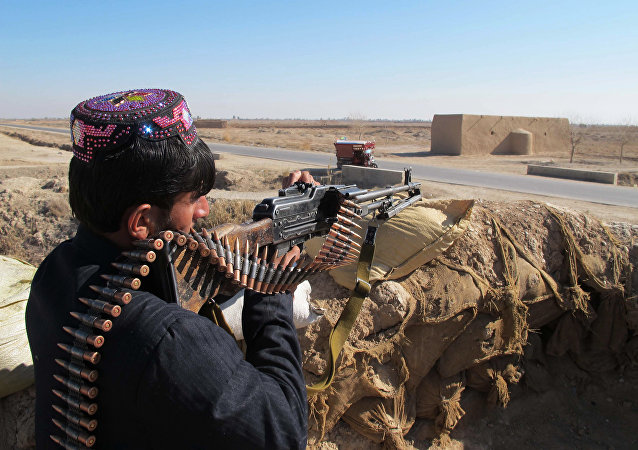 Agente da Polícia Local do Afeganistão toma a posição no distrito de Marjah na província de Helmand durante a batalha contra o Talibã, Afeganistão, 23 de dezembro de 2015