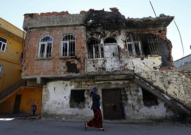 Uma mulher passa por um edifício que foi danificado durante confrontos entre forças de segurança turcas e militantes curdos, na cidade do sudeste de Silvan, na província de Diyarbakir, Turquia, 7 de dezembro de 2015. Foto tirada em 7 de dezembro de 2015. REUTERS / Murad Sezer