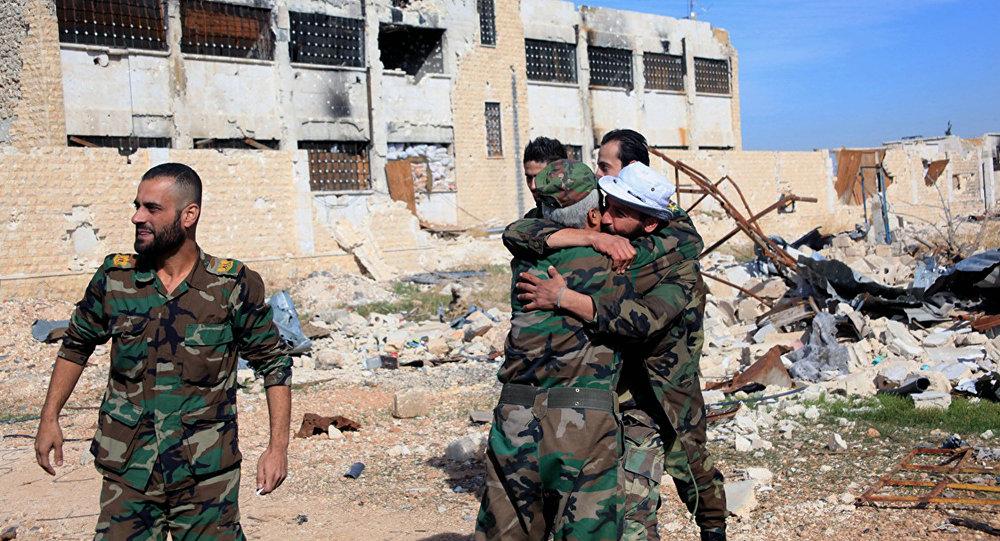 Soldados do governo sírio se abraçam em comemoração dentro da base aérea Kuweires, leste de Aleppo, Síria