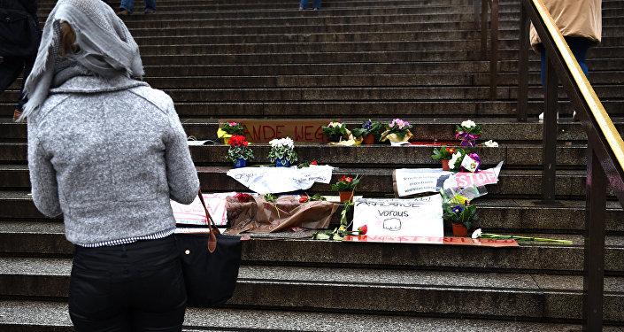 Mulher contempla as flores e cartas contra a violência e as ações de assédio sexual por imigrantes na véspera do Ano Novo, deixadas junto à catedral de Colônia, Alemanha, 11 de janeiro de 2016