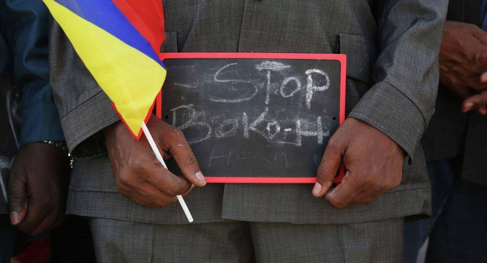 Um homem segurando uma placa Stop Boko Haram