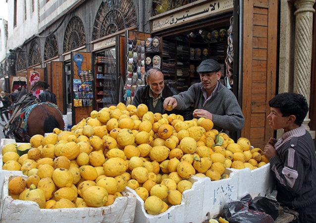 Homem escolha limões no mercado na rua al-Mustaqim em Damasco, Síria