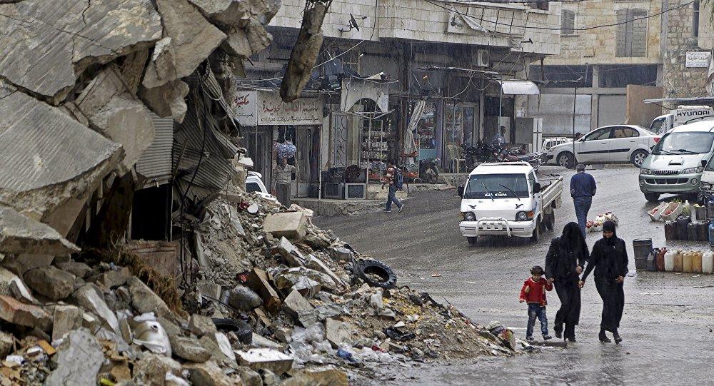Civis na chuva ao lado de um prédio danificado na área de Maaret al-Numat, Síria