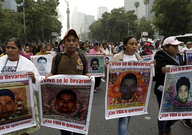 Familiares seguram imagens de alguns dos 43 estudantes desaparecidos de Ayotzinapa, em marcha na Cidade do México