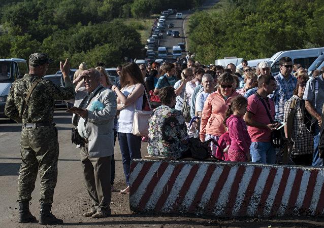 Moradores das regiões de Donetsk e Luhansk esperam para passar por posto de controle do governo ucraniano na estrada de Horlivka para Artemivsk, na região de Donetsk (foto de arquivo)