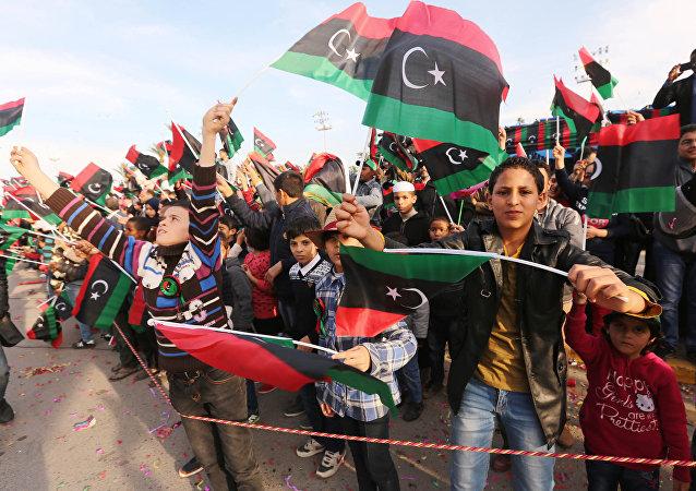 Cidadãos líbios agitam bandeiras nacionais da Líbia durante manifestação em Trípoli em comemoração ao 64 aniversário de independência do país