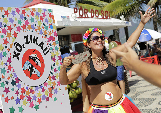 Viviane Oliveira, who's three months pregnant, dances next to a sign that reads in Portuguese : Get out Zika during a street carnival on Ipanema beach in Rio de Janeiro, Brazil, Sunday, Jan. 31, 2016