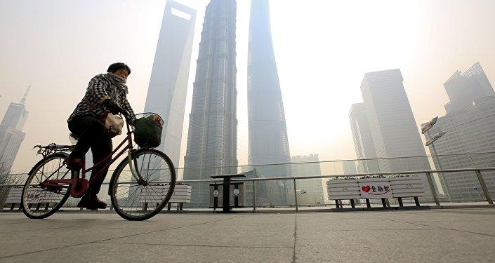 Mulher anda de bicicleta e cobre o rosto para se proteger da poluição em Pudong