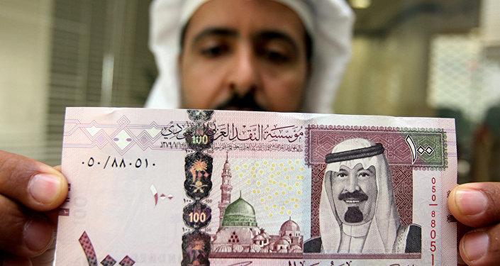 Bancário saudita mostra cédula com o retrato do rei Abdullah bin Abdul Aziz al-Saud em um banco de Riad