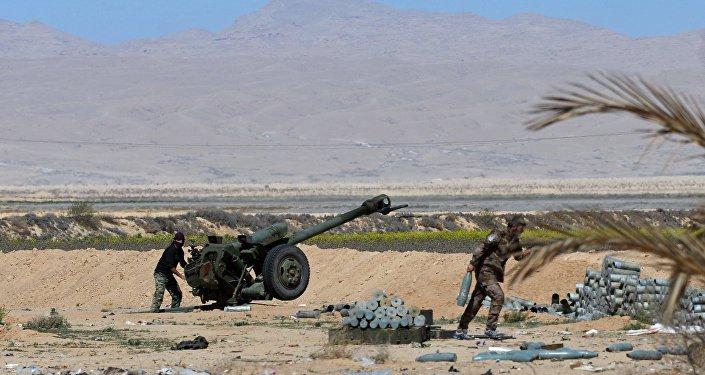 Militares sírios lançam fogo da peça de artilharia D-30 contra as posições de militantes nos arredores de Palmira, Síria, 14 de março de 2016