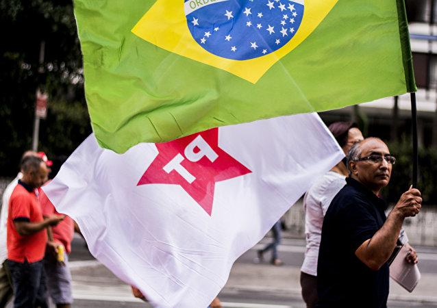 Um manifestante carrega bandeiras do PT e do Brasil no início do ato na Paulista em 18 de março de 2016