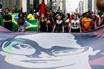 Manifestantes expõem um cartaz com a imagem da presidente Dilma Rousseff