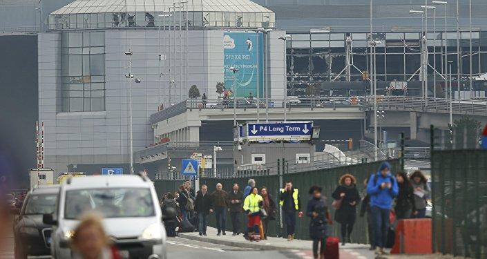Pessoas deixam a cena das explosões no aeroporto de Zaventem, perto de Bruxelas,em 22 de março de 2016