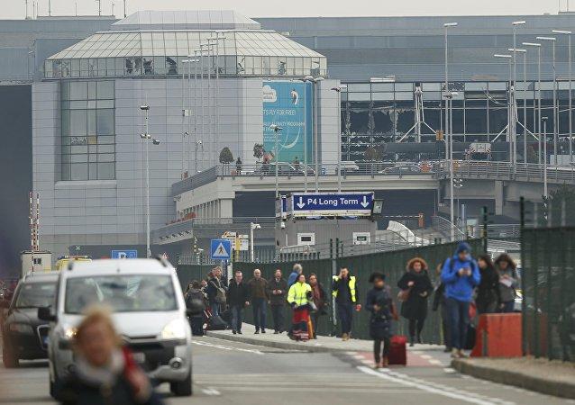 Pessoas deixam a cena de explosões no aeroporto de Zaventem, perto de Bruxelas, Bélgica, 22 de março de 2016