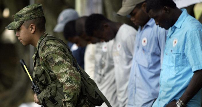 Um soldado do exército colombiano passa na frente de uma fila de guerrilheiros das FARC e do ELN