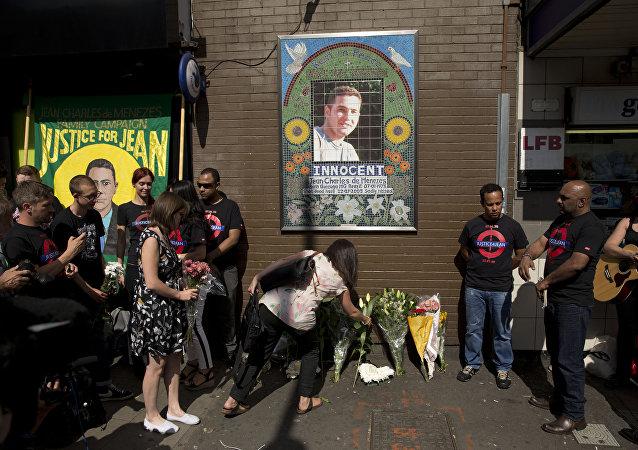 Pessoas trazerem flores à placa memorial na estação Stockwell no dia de 10º aniversário da morte de Jean Charles de Menezes