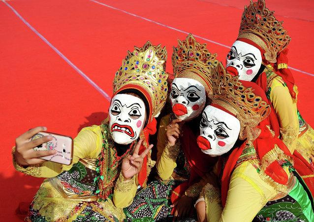 Moças tiram selfie no festival de máscaras para comemorar o aniversário do profeta Maomé, Indonésia