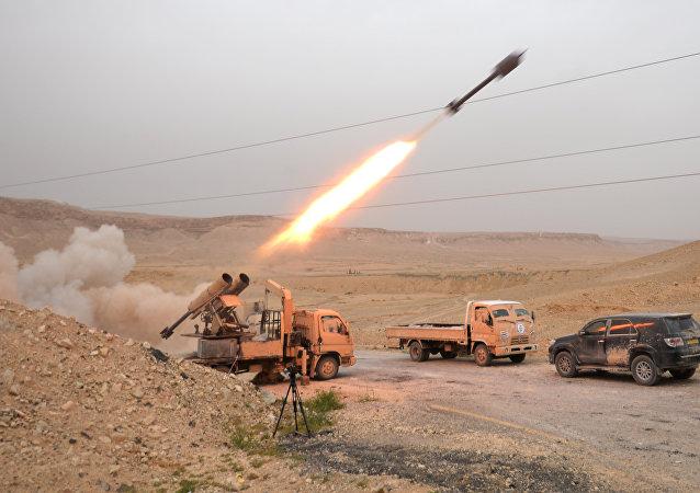 Soldados sírios e agentes do destacamento Falcões do Deserto lançam fogo contra posições de militantes na região de Palmira, Síria, 28 de março de 2016