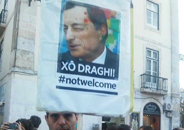 Xô Draghi! Notwelcome, reza este cartaz, usado por manifestantes do Bloco de Esquerda e movimento Rendimento Básico Incondicional, em Lisboa em 7 de abril de 2016