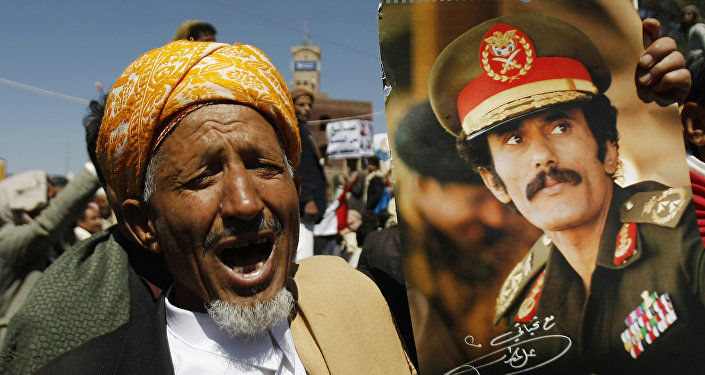 Um homem grita palavras de ordem mostrando um cartaz com a imagem do ex-presidente iemenita Ali Abdullah Saleh durante uma manifestação em 7 de novembro de 2014