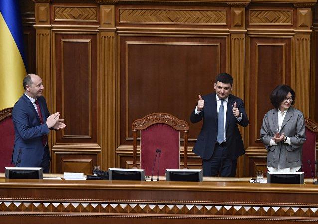 O novo primeiro-ministro da Ucrânia, Vladimir Groisman, no centro da foto, saúda os deputados depois da sua nomeação, em 14 de abril de 2016. Ao lado dele, está Oksana Syroed, vice-presidente do parlamento ucraniano. À esquerda na foto, o presidente do parlamento, Andrei Parubiy