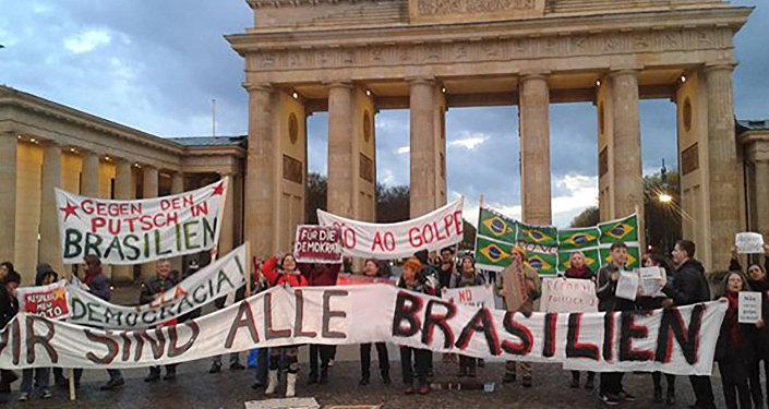 """Na Alemanha, brasileiros se reúnem diante da Porta de Brandemburgo, em Berlim, estendendo cartazes com os dizeres """"Não vai ter golpe"""" e """"Pela Democracia"""""""