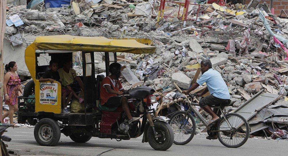 Moradores vão em bicicleta, carro improvisado e a pé pela cidade de Pedernales, Equador, completamente destruída pelo terremoto de 16 de abril.