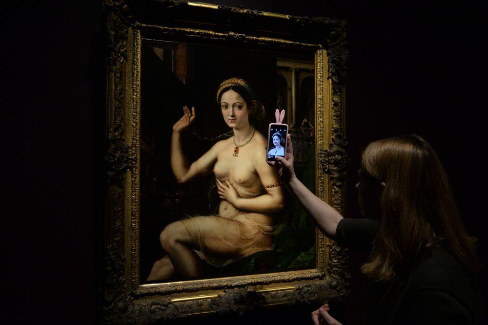 Visitante faz uma foto do quadro de Giulio Pippi (apelidado de Giulio Romano) A Fornarina durante a abertura da exposição Olímpia de Édouard Manet, da coleção do Museu de Orsay, no Museu Pushkin de Belas-Artes em Moscou