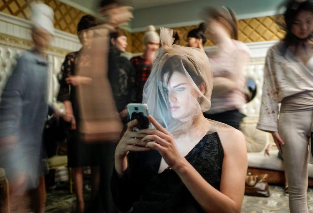 Modelo sentada com celular nos bastidores na Semana da Moda, na cidade de Almaty, Cazaquistão
